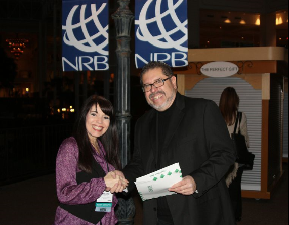 Cheryl Wicker shakes hands with Isaac Hernandez after signing a contract with Parables TV